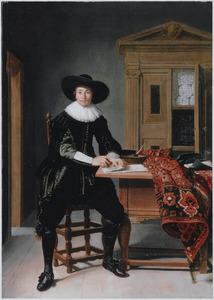 Portret van een man ten voeten uit zittend aan tafel in zijn werkkamer