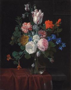Bloemen in een glazen vaas op een deel gedekte stenen plint