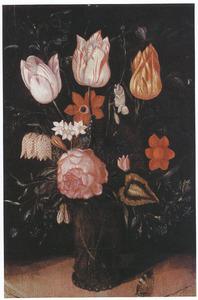 Tulpen en andere bloemen in een glazen beker met braamnoppen