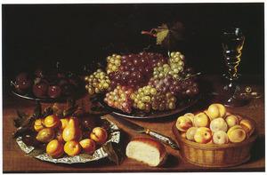 Vruchtenstilleven op een houten tafel met rechts een Venetiaans glas met wijn