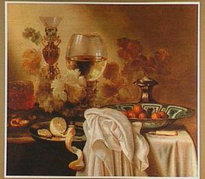 Stilleven met een bekerschroef, glaswerk, een citroen en noten