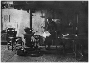 Piet Mondriaan lezend in de woonkamer van zijn atelier