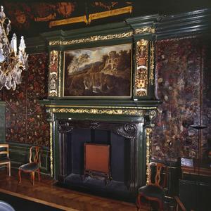 Wand met goudleerbehang en zeventiende-eeuwse schoorsteenbetimmering met houtsnijwerk en schilderstuk