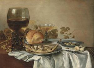 Stilleven met roemer, bokking in moten, uien en brood op een donker kleed met wit servet