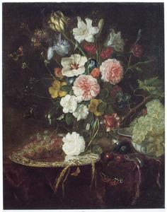 Bloemen in een glazen vaas en druiven op een zilveren schaal en in een porseleinen kom