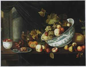 Stilleven op een houten tafel met vruchten in en rond een porseleinen schaal, een roemer met wijn, een zilveren schotel met een krab en een porseleinen kommetje met bessen