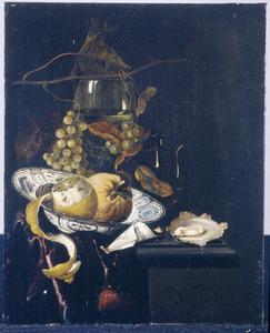 Stilleven met vruchten op een Wan Li-schotel, een oester, een roemer en druiven op een deels met een kleed bedekte stenen plint