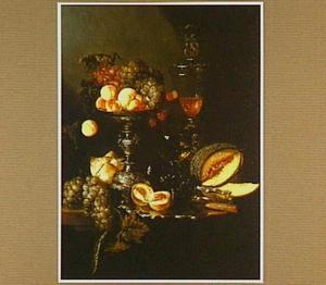 Stilleven met drinkglazen en vruchten, op en rondom een zilveren schaal en tazza, op een tafel met een donker kleed