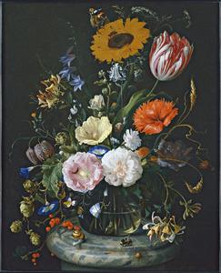 Bloemen in een glazen fles op een marmeren voetstuk