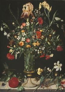 Bloemen in en rondom een hoge glazen vaas op een stenen plint