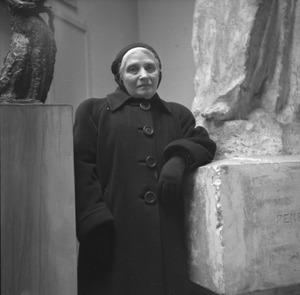 De weduwe van Antoine Bourdelle bij een werk van Bourdelle in het atelier van de beeldhouwer.