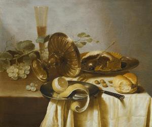 Stilleven met een pastij, half geschilde citroen, druiven, hazelnoten, brood, een glas en gekantelde tazza op een tafel