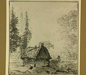 Hut met rieten dak op een open plek in een bos