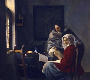 Een jonge vrouw en een man die bladmuziek bestuderen in een interieur