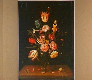 Boeket van tulpen, rozen, anjers en andere bloemen in een glazen vaas