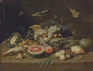 Druiven en walnoten in een porseleinen kom en andere vruchten op een stenen plint