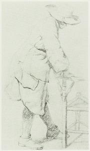 Staande man leunend op een stoel