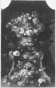Bloemen in en rondom een terracotta vaas op een sokkel