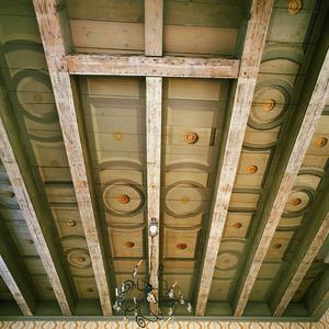 Balkenplafond beschilderd met cirkels, vakken en rozetten