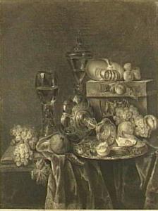 Stilleven met fruit, glas-en zilverwerk, een omgevallen tazza en een doos op een donker kleed