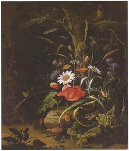 Stilleven van wilde bloemen aan de voet van een eikenboom, voor een grot