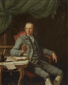 Portret van een 48-jarige  man in een grijs pak, zittend in zijn studeerkamer