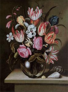 Bloemen in een glazen vaas en schelpen op een stenen plint
