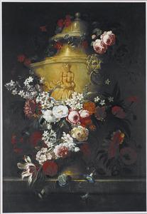 Ornamentele tuinvaas met bloemen op een stenen plint