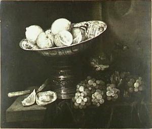 Stilleven met fruit, oesters en faience-schaal op zilveren standaard