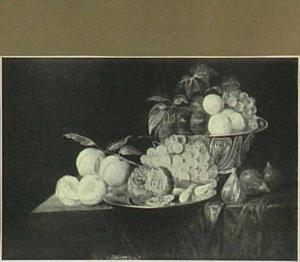 Een tafel met een porseleinen kom met pruimen en druiven, midden voor een tinnen bord met een granaatappel, links drie perziken en rechts drie dadels