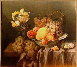 Stilleven met porseleinen schaal met vruchten, een glas met geschilde citroen, oester en geconfijte vrucht, op een (zijden) tafelkleed
