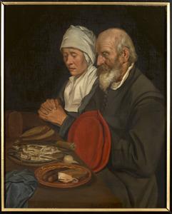 Een paar, biddend voor de maaltijd