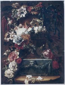 Bloemen in en rondom een tuinvaas op een geornameteerde plint