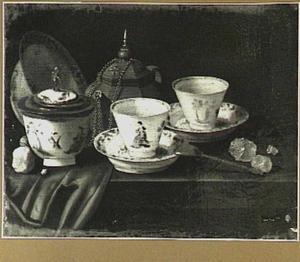 Een Yixing theepot, chinees porseleinen kopjes, suikerpot  en een schotel op een gedeeltelijk met een rood kleed bedekte tafel