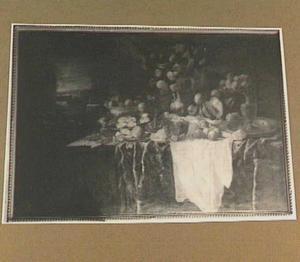 Pronkstilleven met vruchten, bloemen en siervaatwerk op een tafel met geborduurd kleed en wit servet; links een doorkijkje naar buiten