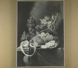 Stilleven van vruchten, oesters en een pronkbeker op een tafel