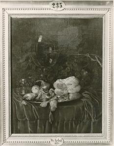 Stilleven met haring, brood, uien, druiven en een roemer op een gedekte tafel
