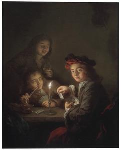 Kaartende jongens bij kaarslicht