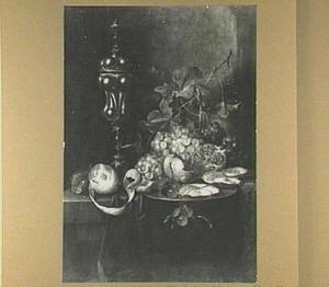Stilleven van vruchten, oesters en een pronkbeker op een stenen plint