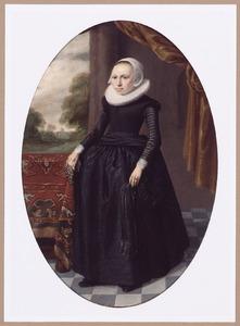 Portret van een vrouw met handschoenen in de rechterhand, staande naast een tafel met een oosters kleed