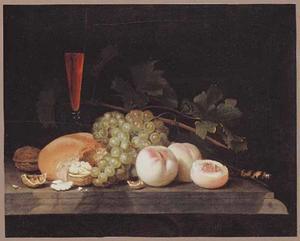 Stilleven van vruchten, brood, een wijnglas en een mes op een stenen plint