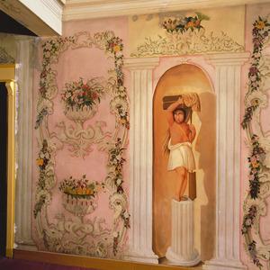 Rocaille-ornamenten met bloemslingers ter weerszijden van een beeld in een nis