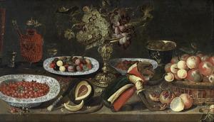 Uitgebreid stilleven met vruchten op schalen en druiven in een tazza, glaswerk en een gekleed aapje op een tafel