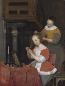Interieur met een jonge vrouw en haar dienstmaagd bij het haar kammen