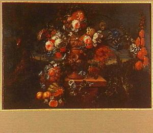 Bloemen in en rondom een geornamenteerde vaas op een voetstuk in een landschap. Ervoor enkele vruchten