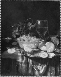 Een porseleinen kom met aardbeien, een roemer en een schotel met oesters en garnalen op een deels met een kleed bedekte tafel
