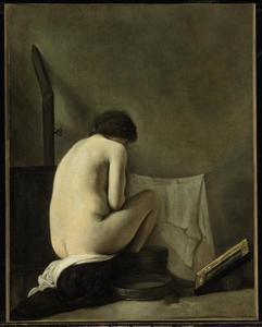 Zittend vrouwelijk naakt bij een kachel tijdens haar toilet