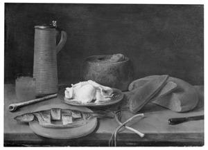 Stilleven van kruik, glas, brood, boter en vis op een tafel
