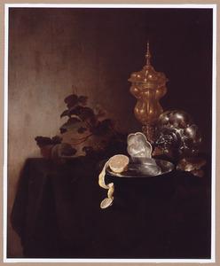 Een akeleibeker, een omgevallen tazza, een tinnen bord met deels geschilde citroen en een tros druiven op een tafel bedekt met een groen kleed