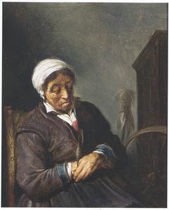 Oude vrouw bij een spinnewiel